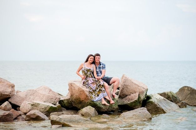 Молодая пара на скалах в море Premium Фотографии