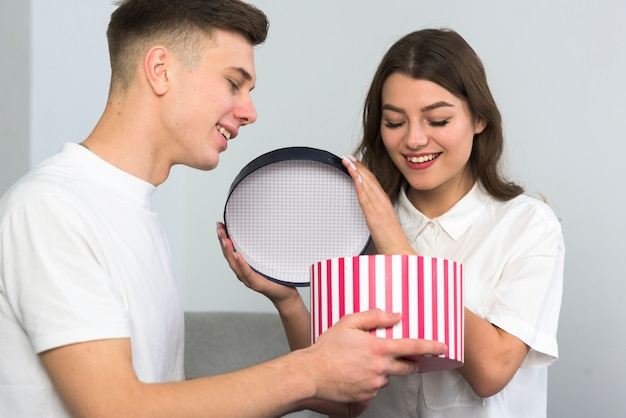 Young couple opening big gift box on couch Free Photo