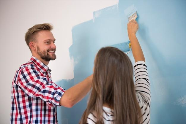 Giovani coppie che verniciano una parete blu Foto Gratuite
