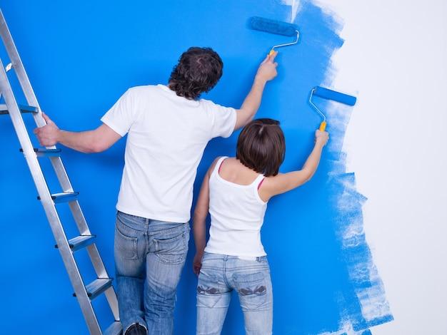 Giovani coppie che dipingono insieme il muro con il rullo Foto Gratuite