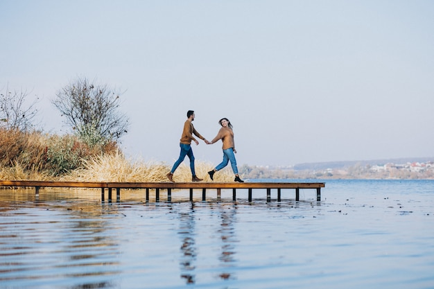 Young couple in park standing by the river standing on the deck bridge Free Photo