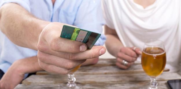 若いカップルはクレジットカードで飲み物の請求書を支払います Premium写真