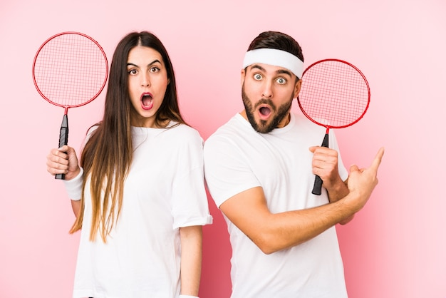 Young couple playing badminton isolated pointing to the side Premium Photo