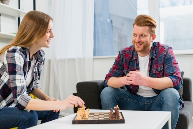 Young couple playing the chessboard in the living room at home Free Photo