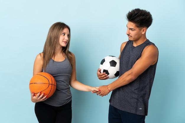 Молодая пара играет в футбол и баскетбол на синем рукопожатии после хорошей сделки Premium Фотографии