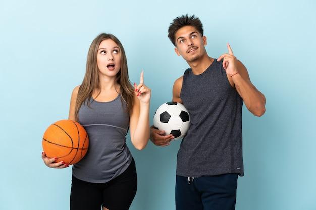 Молодая пара играет в футбол и баскетбол на синем, думая об идее, указывая пальцем вверх Premium Фотографии