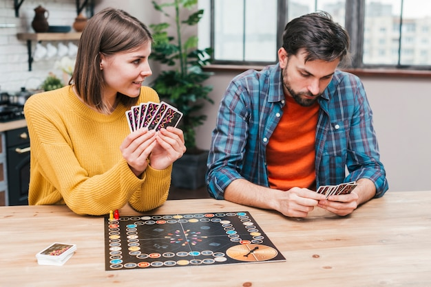 Young couple playing the game board on wooden desk Free Photo