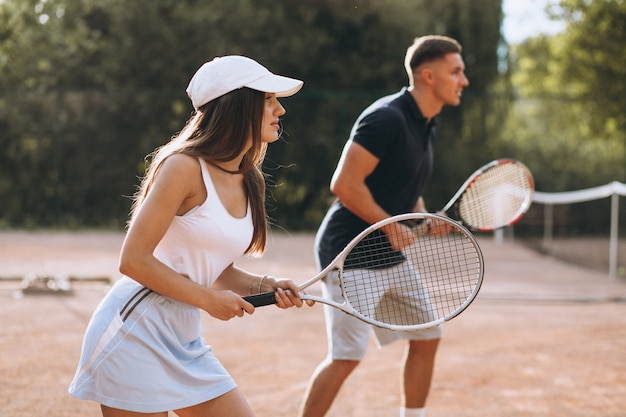 Young couple playing tennis at the court Free Photo