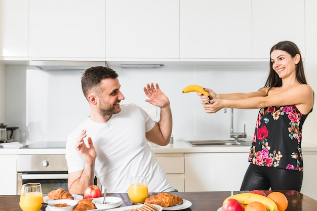 Young couple playing with banana in the kitchen Free Photo