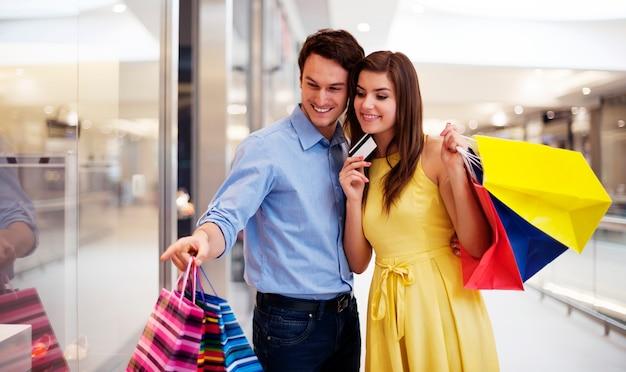 Молодая пара, указывая на окна покупок Бесплатные Фотографии