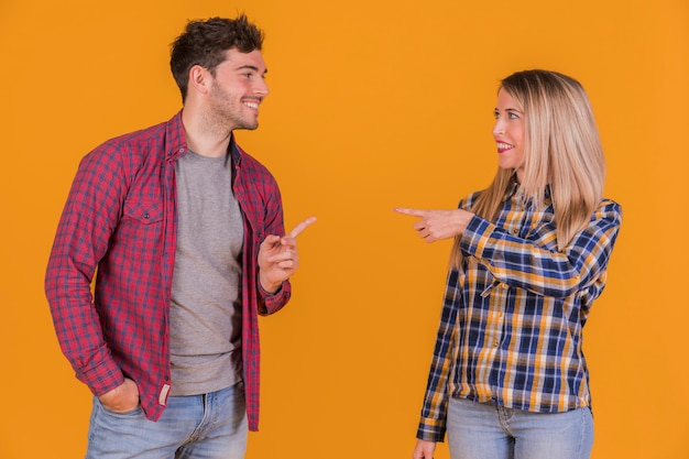Young couple pointing their fingers to each other against an orange backdrop Free Photo