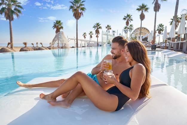 Young couple on pool hammock at beach resort Premium Photo