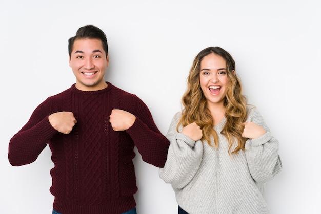Молодая пара позирует в белой стене удивленно указывая пальцем, широко улыбаясь Premium Фотографии