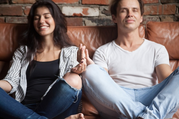 Young couple practicing yoga meditating together at home on sofa Free Photo