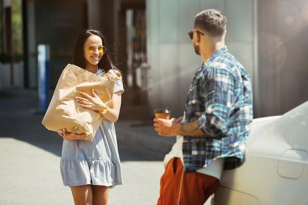 晴れた日に車で休暇旅行の準備をしている若いカップル。女性と男性が買い物をし、海、川沿い、または海に行く準備ができています。関係、休暇、夏、休日、週末の概念。 無料写真