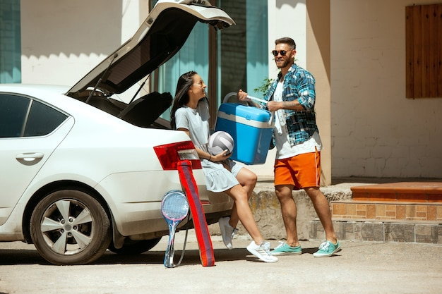 晴れた日に車で休暇旅行の準備をしている若いカップル。スポーツ用品を積み上げる女性と男性。海、川沿い、または海に行く準備ができています。関係の概念、夏、週末。 無料写真