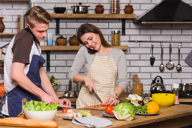 Young couple preparing salad during smartphone conversation Free Photo