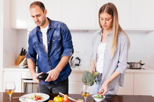 Young couple preparing salad with wineglasses on the wooden table Free Photo