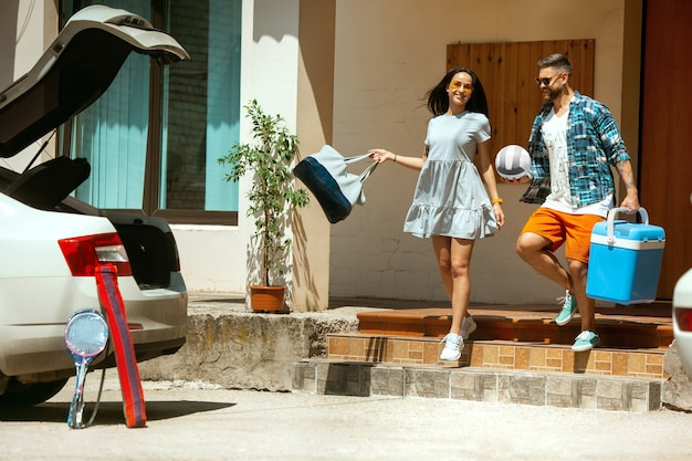 Young couple preparing for vacation trip on the car in sunny day. woman and man stacking up sport equipment. ready for going to sea, riverside or ocean. concept of relationship, summer, weekend. Free Photo