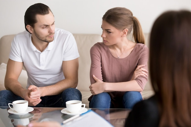 Young couple at psychologist, looking at each other with hate Free Photo