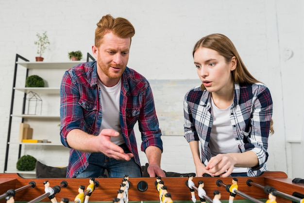 Young couple quarreling while playing the table soccer game Free Photo