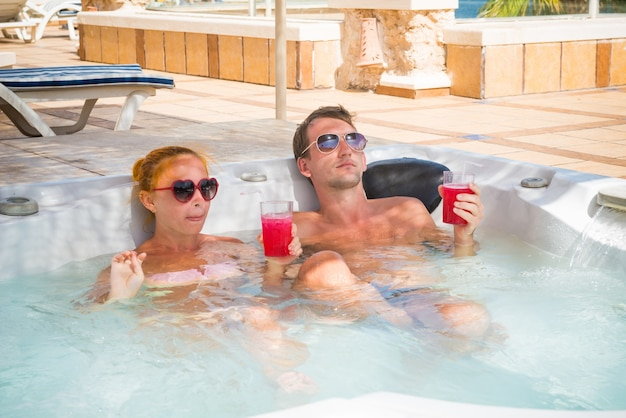 Young couple relaxing in jacuzzi pool Free Photo