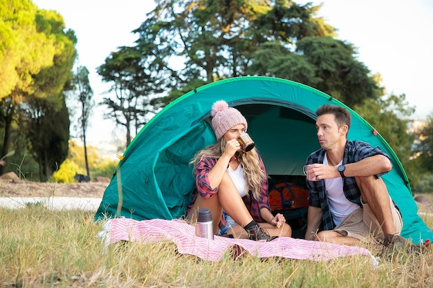 Young couple relaxing on nature together and drinking tea. caucasian long-haired woman in hat sitting in tent together with man and chatting. tourism, adventure and summer vacation concept Free Photo