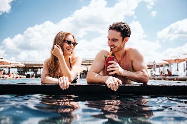 Молодая пара, отдыхая в бассейне Premium Фотографии