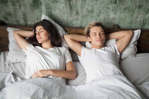 Young couple resting sleeping well together in comfortable bed Free Photo