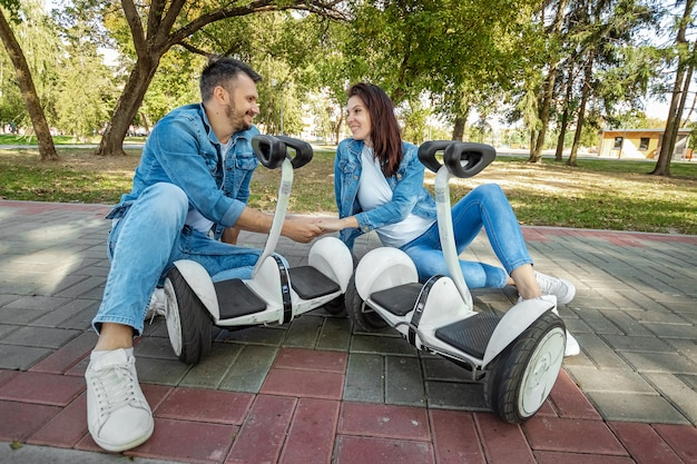 A young couple riding a hoverboard in a park Premium Photo