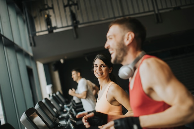 Young couple running on treadmills in modern gym Premium Photo