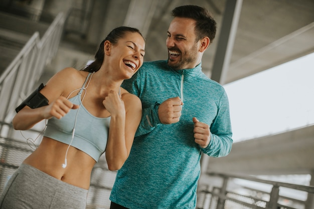 Young couple running in urban enviroment Premium Photo