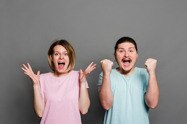 Young couple screaming with joy against grey background Free Photo