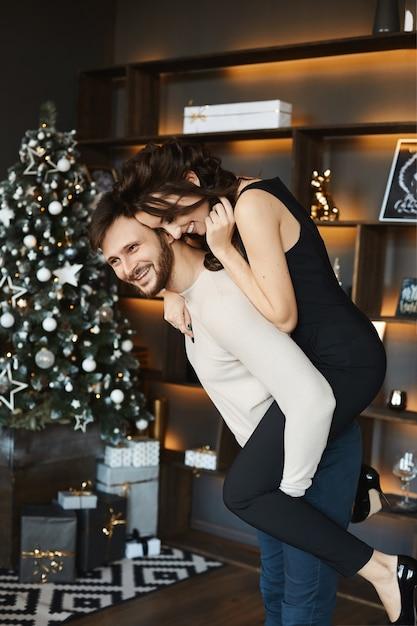 若いカップルはクリスマスの背景の近くに座っています Premium写真