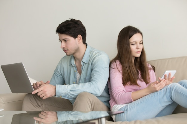 Young couple sitting back to back using laptop computer Free Photo