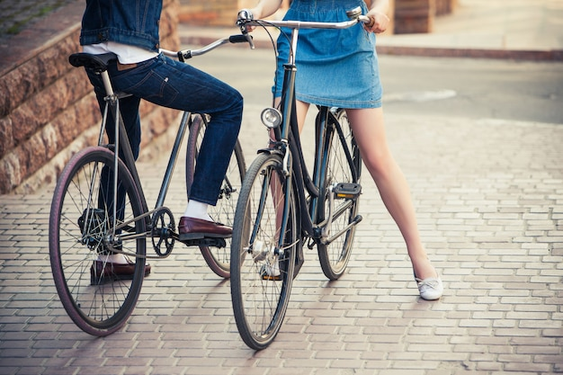 Young couple sitting on a bicycle opposite the city Free Photo