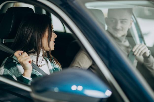 Giovani coppie che si siedono in automobile in una sala d'esposizione dell'automobile Foto Gratuite