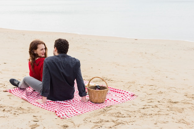 Young couple sitting on coverlet on sea shore Free Photo