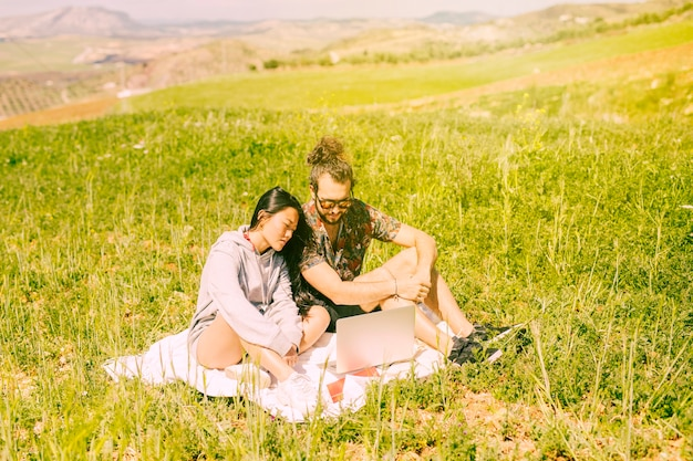 Young couple sitting in field with laptop Free Photo