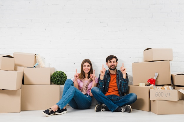Young couple sitting on floor holding their fingers upward sitting between the cardboard boxes Free Photo