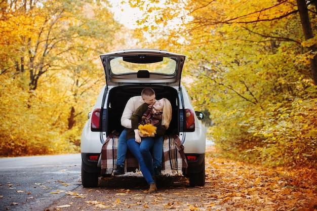 Молодая пара, сидя в багажнике автомобиля на дороге осенью Premium Фотографии