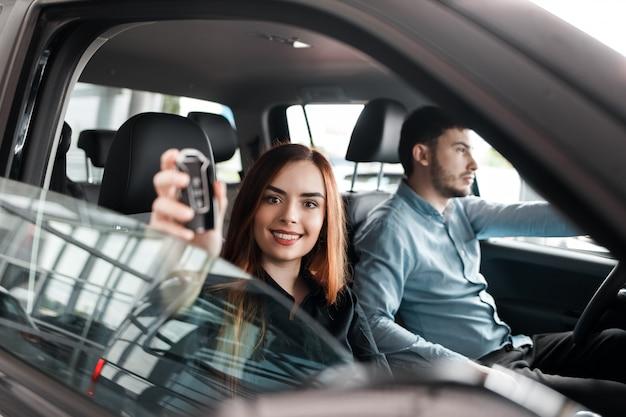 Молодая пара сидит в своей новой машине Premium Фотографии