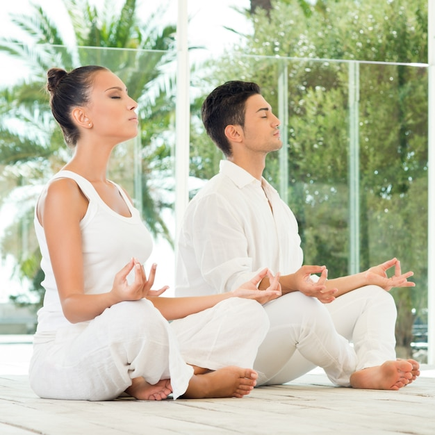 Young couple sitting in a lotus pose and meditating Premium Photo