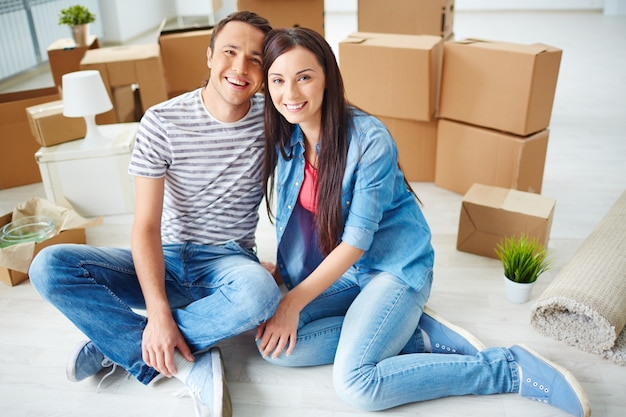 Young couple sitting on floor with moving boxes Free Photo