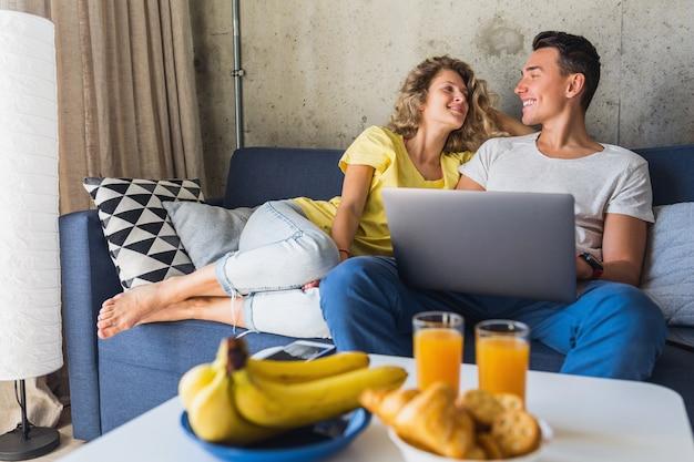 ノートパソコンで探している自宅のソファーに座っている若いカップル 無料写真