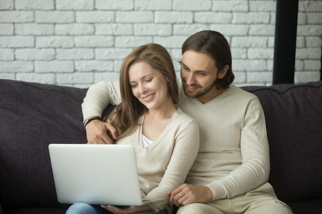 Young couple sitting on sofa hugging using laptop at home Free Photo