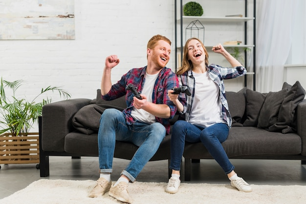 Young couple sitting on sofa playing the video game in the living room Free Photo