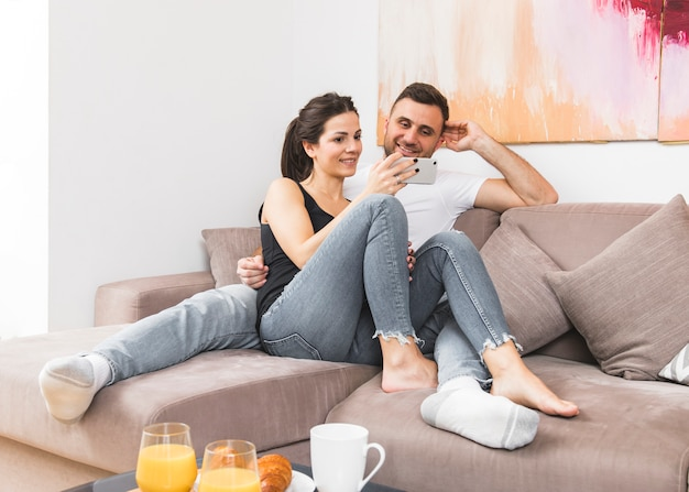 Young couple sitting on sofa watching video on mobile phone at home Free Photo