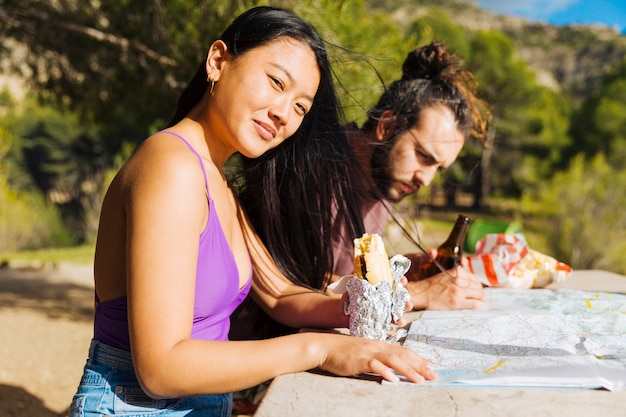 Young couple sitting at table with map and snack Free Photo