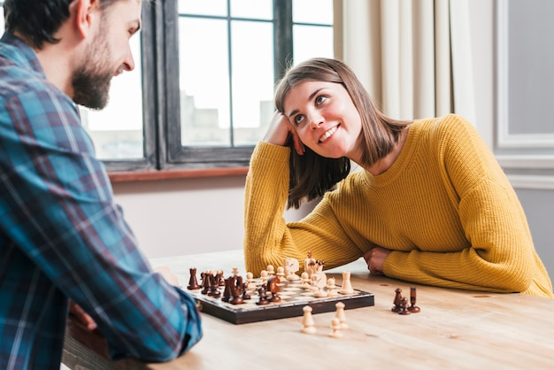 Young couple sitting together playing the chess at home Free Photo